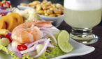 """Peruvian ceviche with king prawn accompanied by sweet potatoes, corn, cancha (fried corn) and the Peruvian cocktail called """"Pisco Sour"""" (Selective Focus, Focus on the front of king prawn)"""